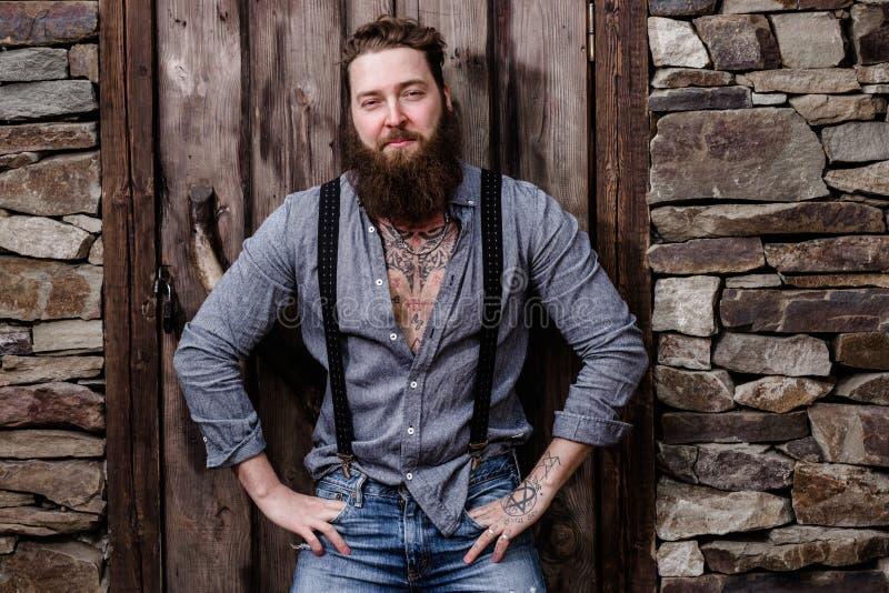Il forte uomo brutale con una barba ed i tatuaggi sulle sue mani vestite in abbigliamento casual alla moda posa sui precedenti di fotografia stock libera da diritti