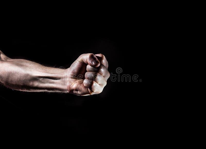 Il forte uomo maschio ha alzato il pugno su un fondo nero, il potere, la guerra, p fotografie stock libere da diritti