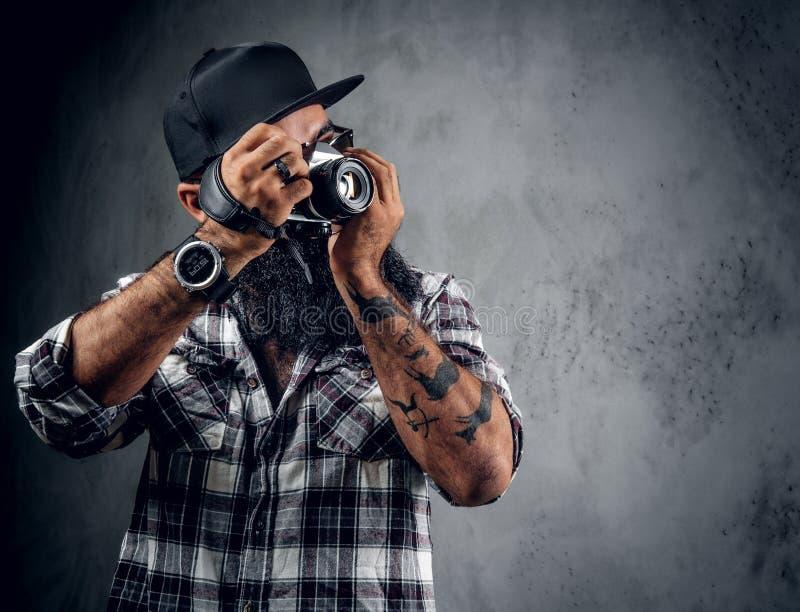 Il fotografo barbuto tiene la macchina fotografica compatta di DSLR sopra fondo grigio fotografia stock libera da diritti