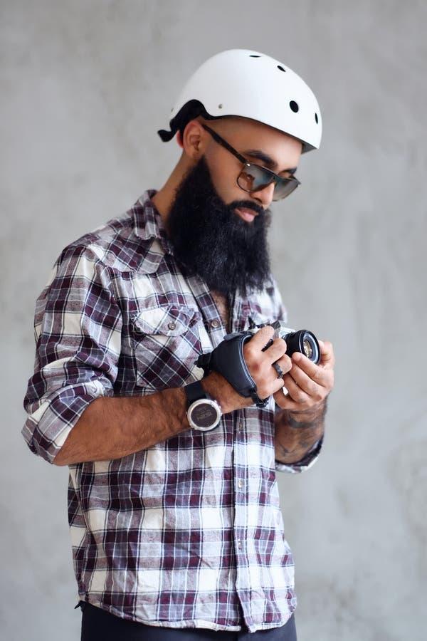 Il fotografo barbuto tiene la macchina fotografica compatta di DSLR sopra fondo grigio fotografie stock