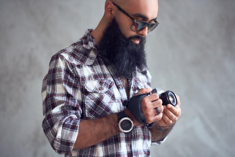 Il fotografo barbuto tiene la macchina fotografica compatta di DSLR sopra fondo grigio fotografia stock