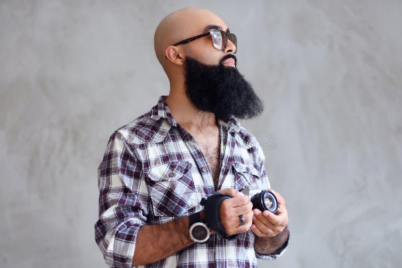 Il fotografo barbuto tiene la macchina fotografica compatta di DSLR sopra fondo grigio immagini stock