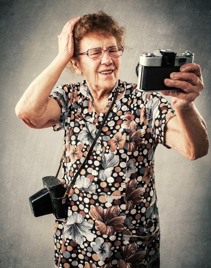 Il fotografo della nonna fa il selfie immagini stock