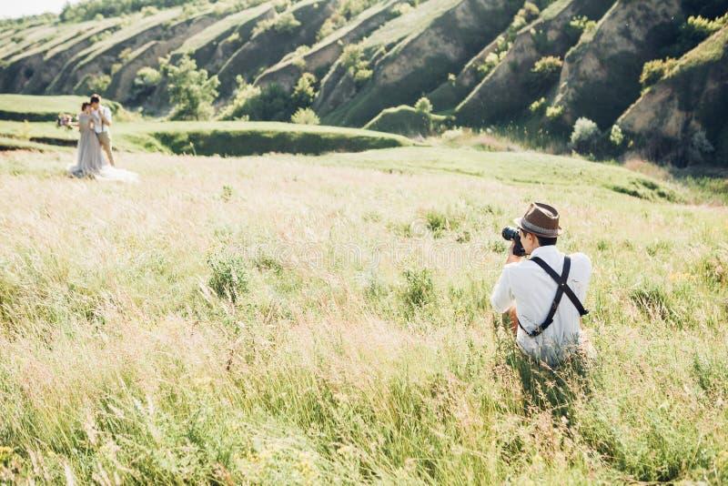 Il fotografo di nozze prende le immagini della sposa e dello sposo in natura, foto di arti fotografie stock