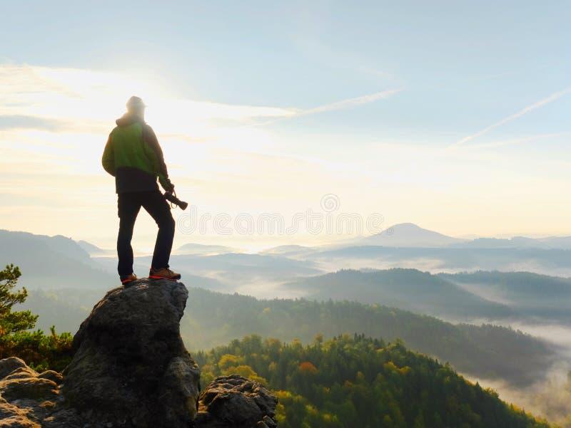 Il fotografo esamina il paesaggio ed ascolta il silenzio L'uomo prepara la macchina fotografica prende le foto fotografia stock libera da diritti