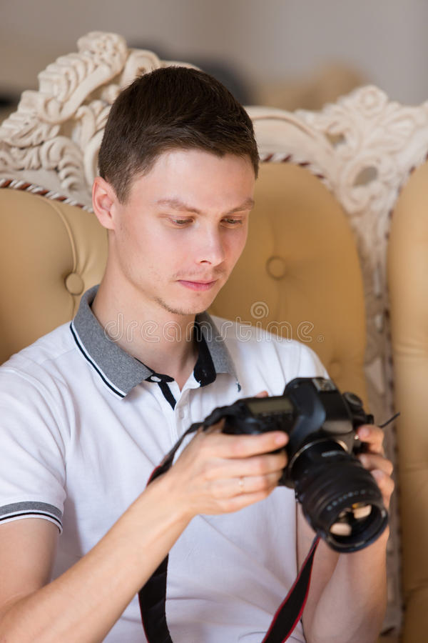 Il fotografo guarda in camera fotografie stock