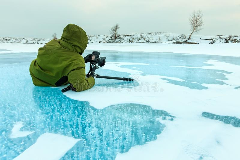 Il fotografo prende le bolle delle immagini del metano congelate in ghiacciata il lago Baikal, Russia fotografia stock libera da diritti
