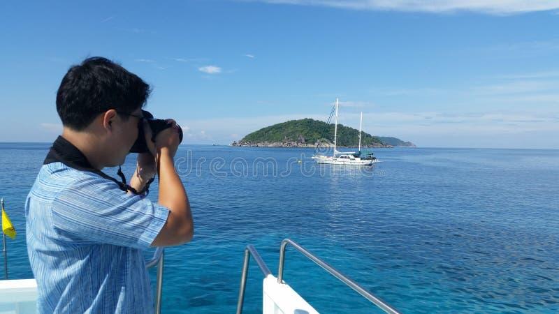 Il fotografo prende una foto della barca e dell'isola in Tailandia fotografia stock libera da diritti