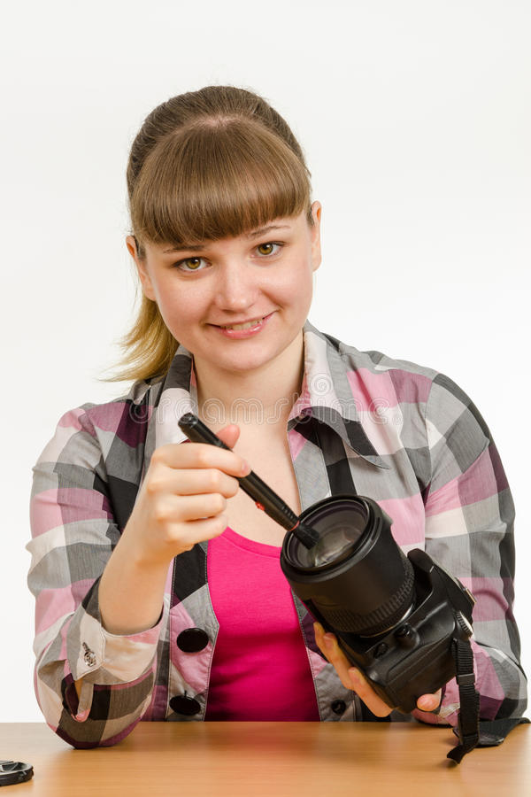 Il fotografo pulisce la parte anteriore della lente sulla macchina fotografica ed ha esaminato la struttura fotografia stock