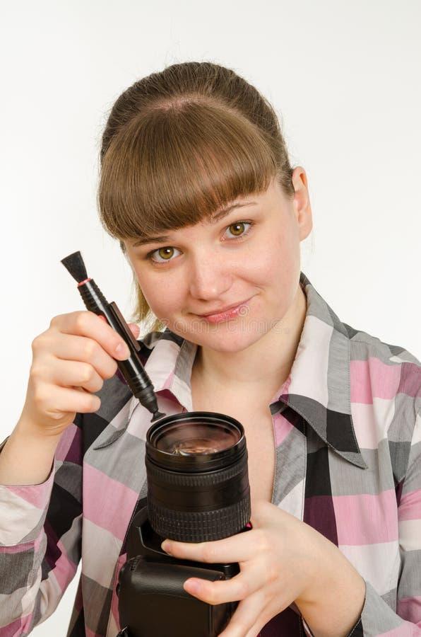 Il fotografo pulisce la parte anteriore della lente sulla macchina fotografica ed ha esaminato la struttura fotografie stock