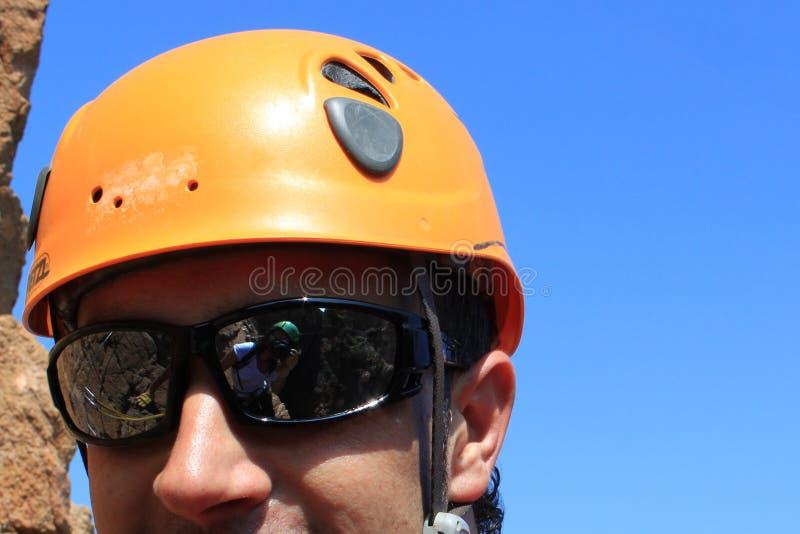 Il fotografo riflette nell'alpinista degli occhiali da sole fotografie stock
