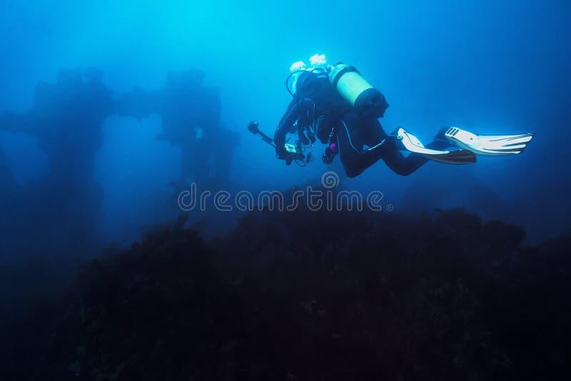 Il fotografo sottomarino si tuffa verso un naufragio fotografia stock libera da diritti