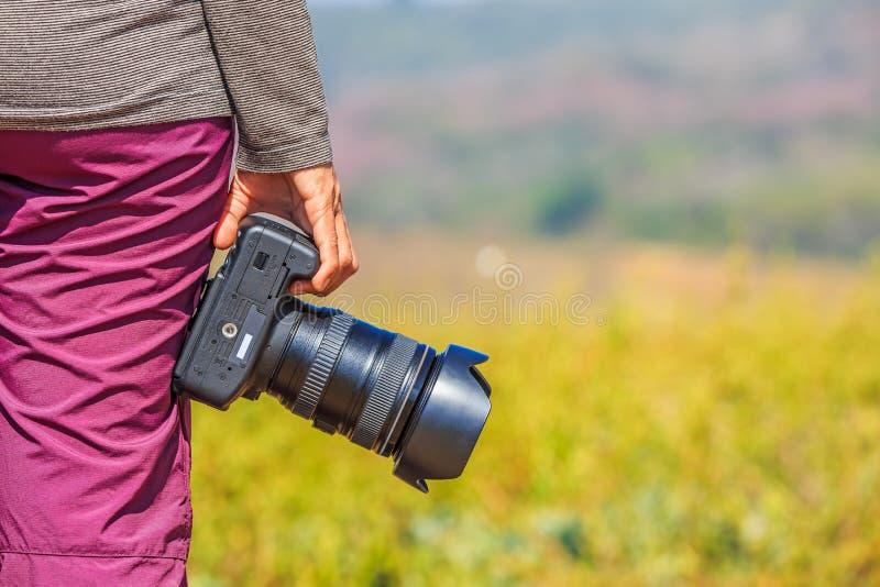 Il fotografo tiene la sua macchina fotografica di DSLR fotografie stock libere da diritti