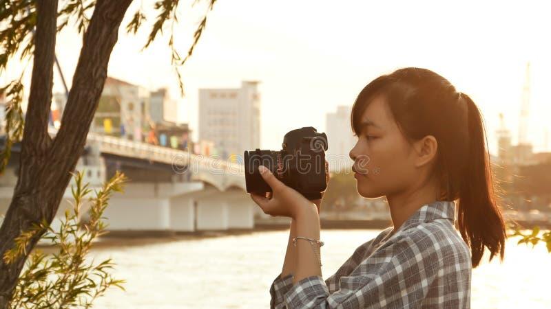 Il fotografo vietnamita della ragazza prende le immagini della natura nel centro urbano al tramonto fotografia stock