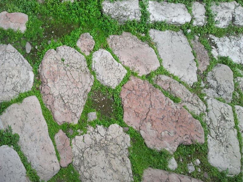 Il frammento di una strada antica di Roman Empire ha pavimentato con le pietre lucidate enormi Manufatto antico del monumento di  fotografia stock