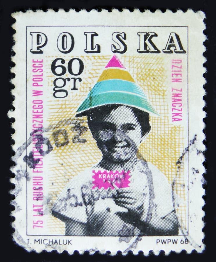 Il francobollo della Polonia mostra il bambino che tiene il bollo simbolico, 75 anni di movimento filatelico in Polonia, Cracovia immagini stock
