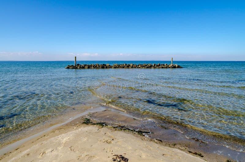 Download Il Frangiflutti Davanti Alla Spiaggia Con Acqua Bassa E L'incrocio Ondeggia Fotografia Stock - Immagine di ciottoli, vista: 117978622