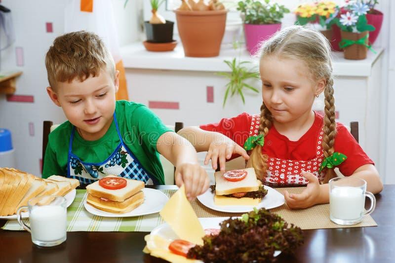 Il fratello allegro e la sorella preparano la prima colazione immagine stock