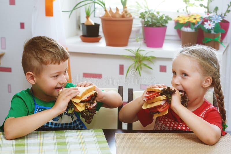 Il fratello allegro e la sorella preparano la prima colazione fotografie stock libere da diritti
