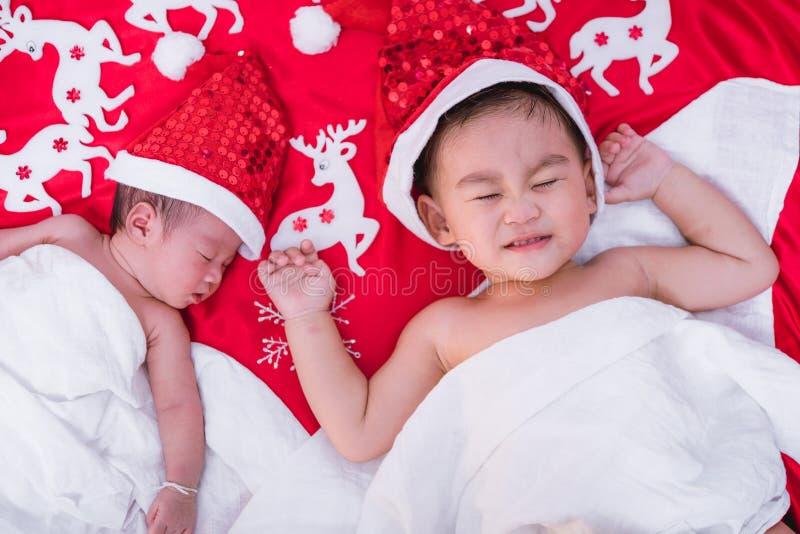 Il fratello del ragazzo del bambino e l'infante del neonato della ragazza della sorella hanno cappello rosso di Santa immagini stock