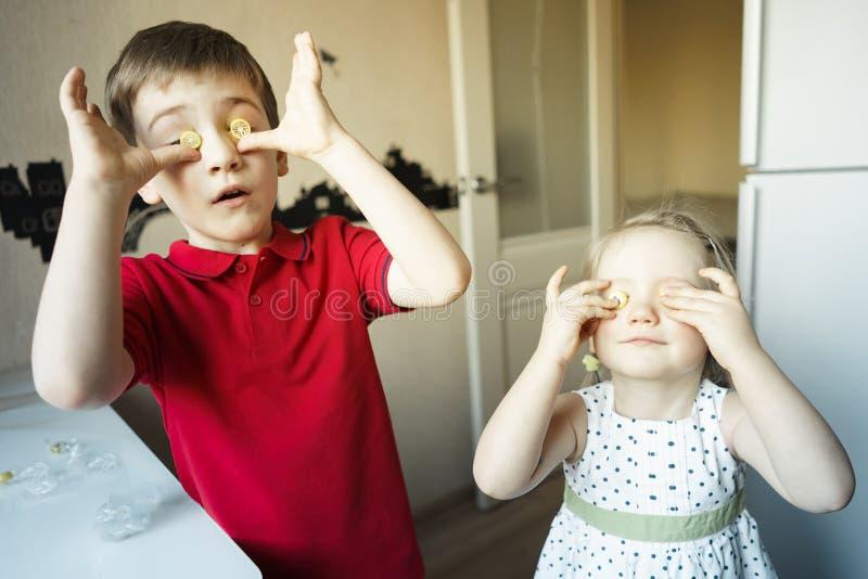 Il fratello e la sorella divertenti chiudono i loro occhi con la caramella come i vetri immagini stock libere da diritti