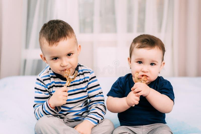 Il fratello e la sorella mangiano le lecca-lecca sotto forma di gallo fotografia stock