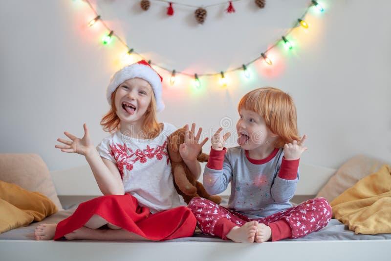 Il fratello e la sorella si siedono su un letto immagine stock