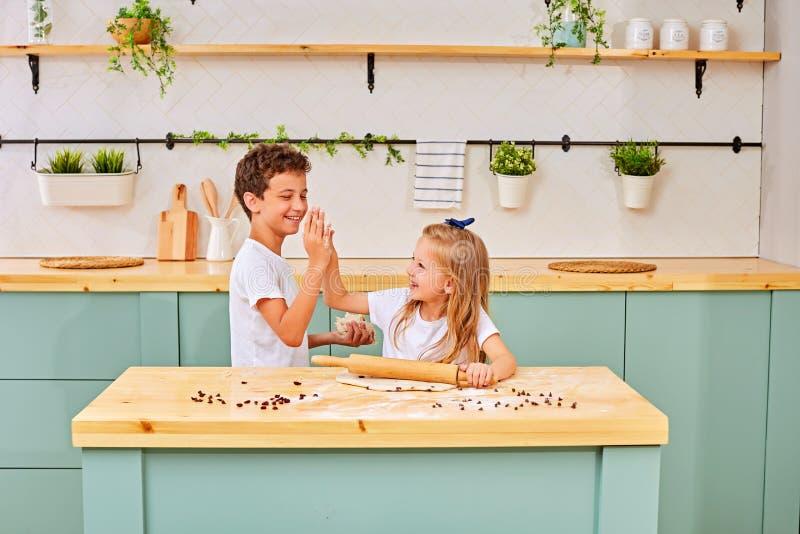 Il fratello e la sorella stanno cucinando i biscotti e stanno divertendo nella cucina fotografia stock