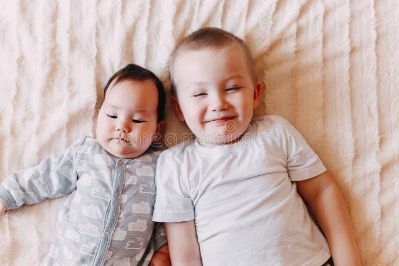 Il fratello e la sua sorellina allegra che si trovano sullo sbadiglio della ragazza del letto immagini stock
