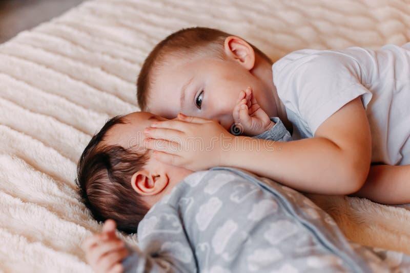 Il fratello e la sua sorellina allegra che si trovano sullo sbadiglio della ragazza del letto fotografia stock