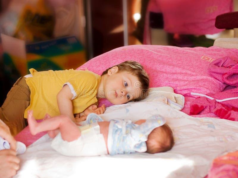 Il fratello maggior esamina il bambino appena nato fotografia stock libera da diritti