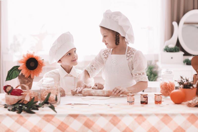 Il fratello piccolo e la sorella preparano il pranzo nella cucina domestica fotografia stock libera da diritti