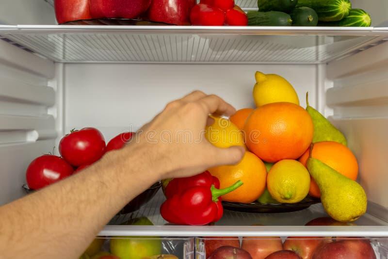 Il frigorifero è riempito di verdure, frutti La mano prende l'alimento dal frigorifero immagini stock