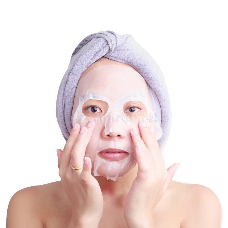 Il fronte asiatico della giovane donna, ragazza che applica il facial pela la maschera fotografia stock libera da diritti