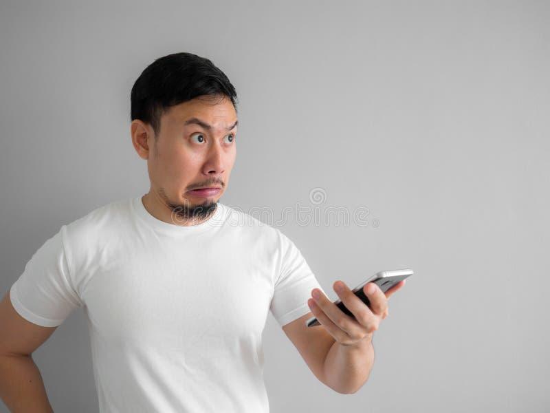 Il fronte colpito e spaventoso dell'uomo ottiene urlato dallo smartphone Vedi la s immagine stock libera da diritti