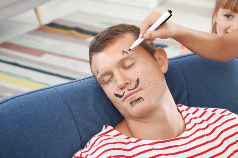 Il fronte del padre della pittura del bambino mentre lui che dorme fotografia stock