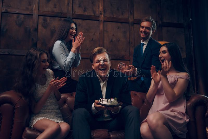 Il fronte dell'uomo bello coperto in torta di compleanno immagini stock