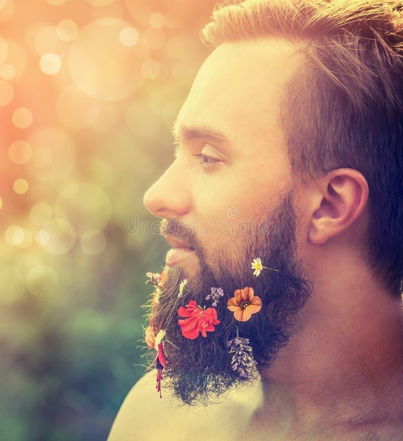 Il fronte dell'uomo nel profilo con una barba con i fiori la sua barba su sfondo naturale con bokeh immagine stock libera da diritti