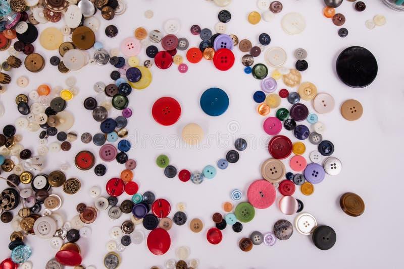 Il fronte sorridente ha creato con i bottoni di cucito assortiti su fondo bianco fotografia stock libera da diritti