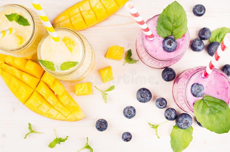 Il frullato giallo e viola di recente mescolato della frutta in barattoli di vetro con paglia, le foglie di menta, le fette del m fotografia stock