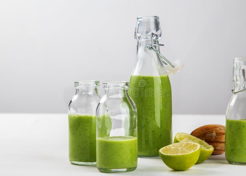 Il frullato verde sano fatto fresco è servito in bottiglie su fondo bianco Frutta e verdure ed ingredienti dei semi intorno fine fotografia stock