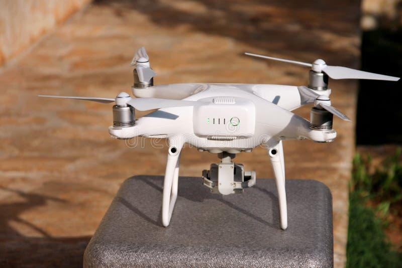 Il fuco bianco del quadcopter con la macchina fotografica digitale 4K sul supporto è pronto affinchè decolla voli in aria per pre immagine stock libera da diritti