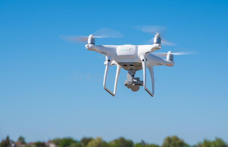 Il fuco moderno, quadrocopter è nell'aria contro lo sfondo del cielo e dell'erba fotografia stock libera da diritti