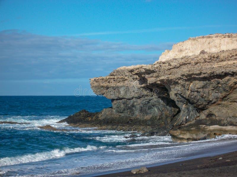 Il fuertoventura dell'isola rocciosa con le montagne, la spiaggia ed il cielo blu fotografia stock