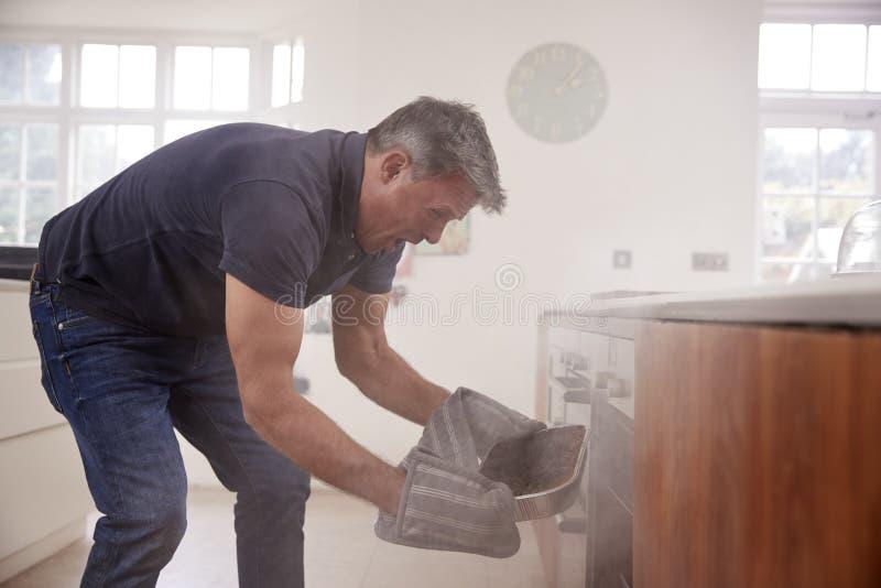 Il fumo di apertura dell'uomo invecchiato mezzo ha riempito il forno nella cucina fotografia stock