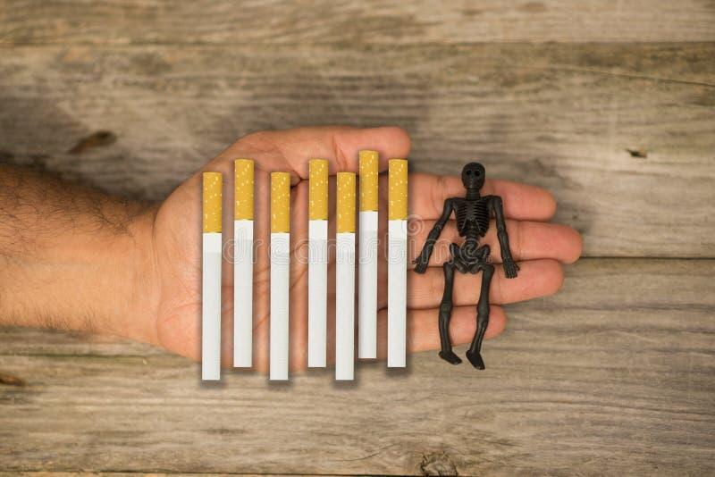 Il fumo uccide il concetto suggerito da molti sigarette e cranio umano a disposizione di un fumatore immagini stock libere da diritti