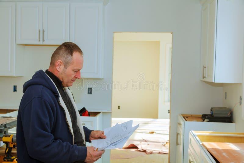 Il funzionamento del carpentiere tiene un piano per l'installazione degli armadi da cucina fotografia stock libera da diritti