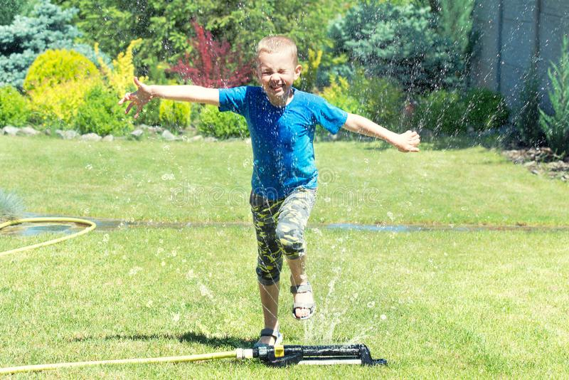 Il funzionamento del ragazzo sullo spruzzatore del prato inglese che gioca con acqua spruzza Giorno di vacanze estive immagini stock libere da diritti