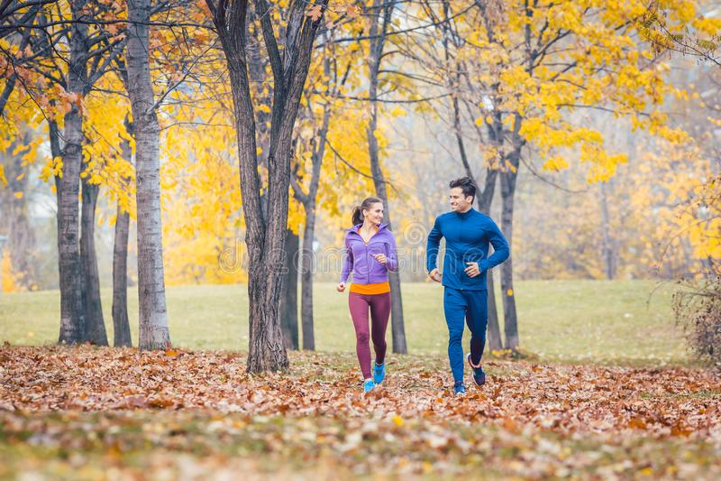 Il funzionamento dell'uomo e della donna in autunno parcheggia per lo sport immagini stock