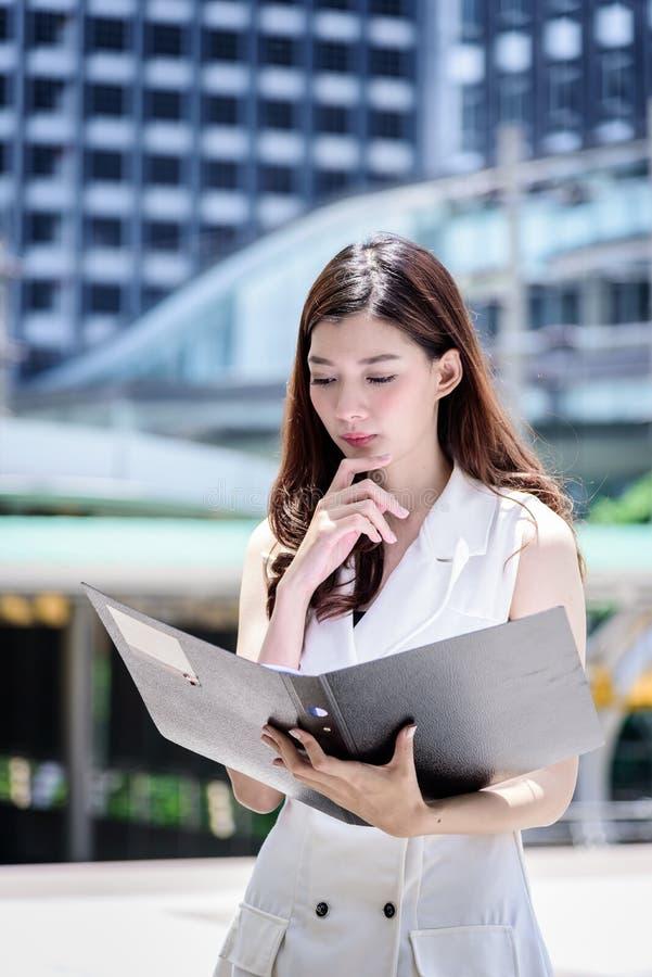 Il funzionamento e l'operazione asiatici della donna di affari in ufficio esterno fotografia stock